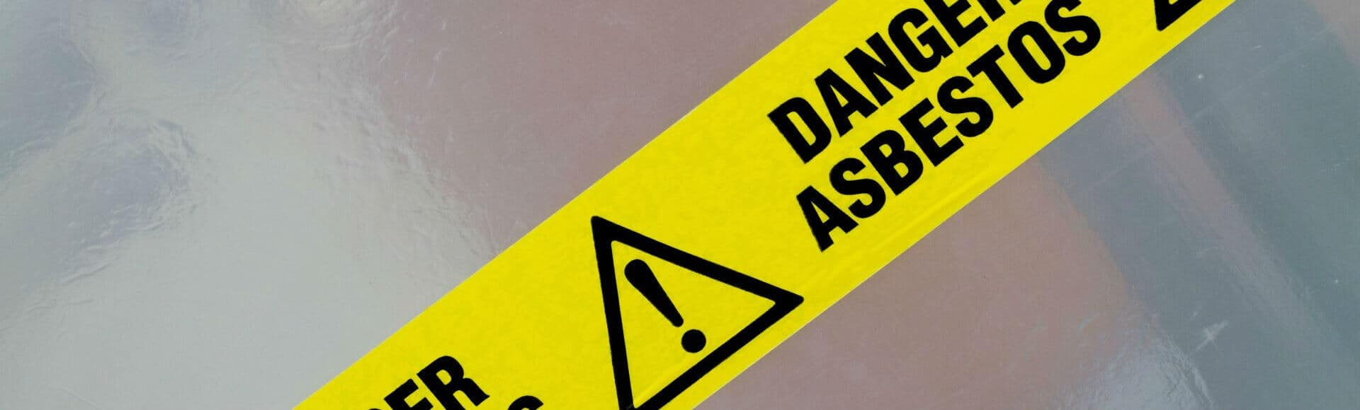 Danger Asbestos yellow warning tape close up